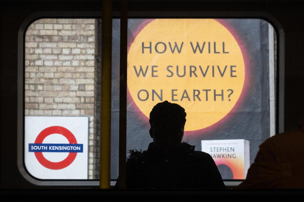 "A sign advertising a book titled ""How Will We Survive On Earth?"" is seen on an underground station platform"