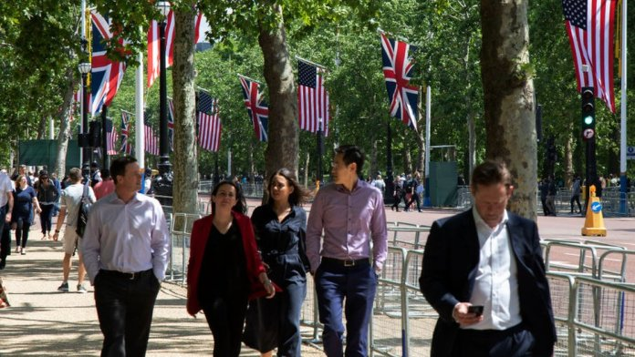 People walk by US and UK flags