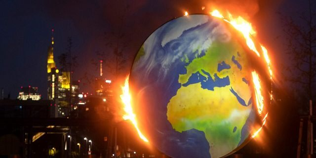"""A makeshift globe burns in front of the European Central Bank in Frankfurt, Germany, Wednesday, Oct. 21, 2020. Activists of the so-called """"KoalaKollektiv,"""" an organization asking for climate justice, protested with the burning of the globe against the ECB's climate policy. (AP Photo/Michael Probst)"""