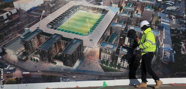 A construction worker passes an artist's impression of AFC Wimbledon's new stadium at Plough Lane