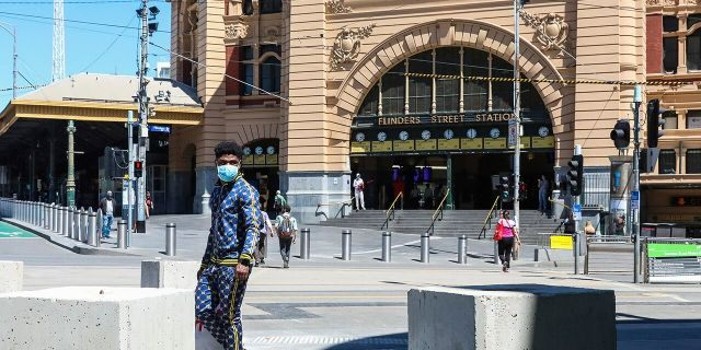 A man wearing a mask walks past Flinders Street Station in Melbourne, Australia, Wednesday, Oct. 28, 2020. In Melbourne, Australia's former coronavirus hotspot, restaurants, cafes and bars were allowed to open and outdoor contact sports can resume Wednesday, emerging from a lockdown due to the coronavirus outbreak. (AP Photo/Asanka Brendon Ratnayake)