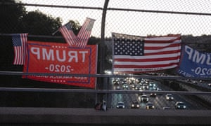 Pro-Trump flags hang from a fence at an overpass on a highway in Lafayette, California.