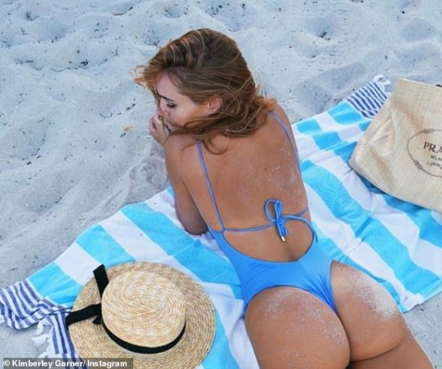 It's a bum deal: The frustrated Kimberley showed off her incredible physique while striking a series of poses on a blue and white striped beach towel