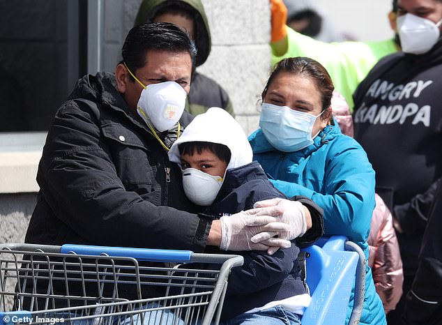 Because masks reduce the amount of particles inhaled, two doctors say face coverings could be a way to generate immunity until there is a vaccine. Pictured: People wearing masks and gloves wait to enter a Walmart in Uniondale, New York, April 17