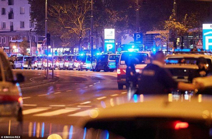 A line of police vans in the city centre last night as a manhunt was launched to find at least one other attacker