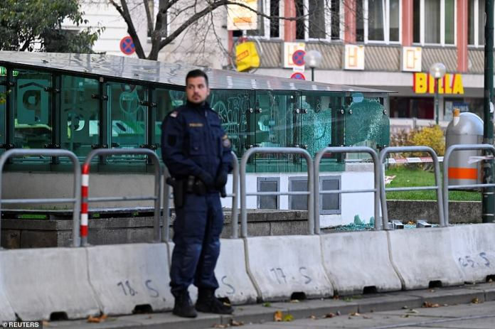 Police officer stands guard this morning next to a shattered glass bus shelter following gun battles in the capital last night