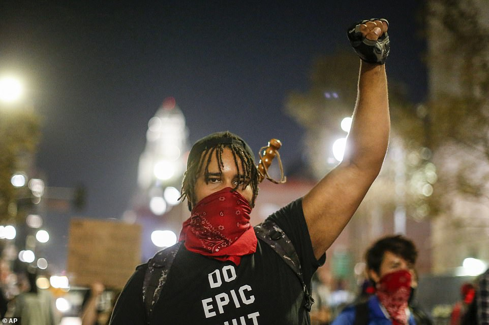 CALIFORNIA: A man raises his fist during a protest in Los Angeles as uncertainty continued over the result of the election