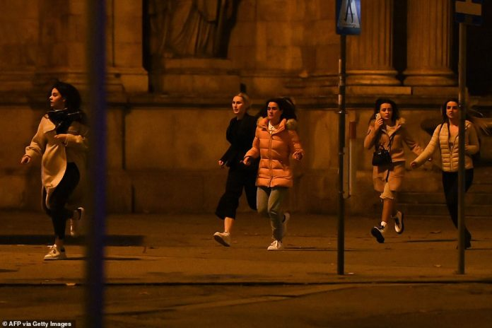 Women run away from the first district near the state opera, central Vienna as shots ring out following several attacks in the city