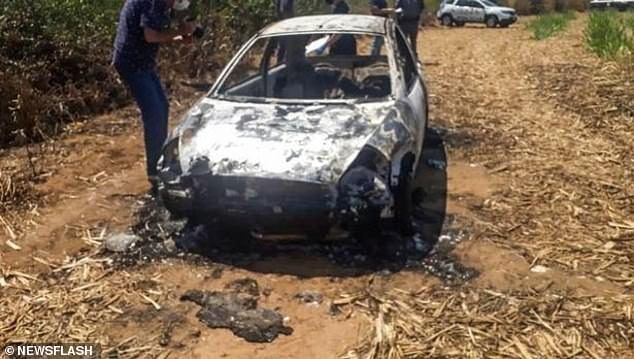 An investigator takes photos the burned vehicle following the October 17 attack in São Paulo, Brazil. The gruesome crime left two people dead, 24-year-old Priscila Ferreira da Silva, who was four months pregnant, and her 39-year-old friend, Ely Carlos dos Santos