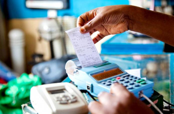 A trader retrievesa receipt from an EBM. The amended law reinforces ministerial powers to fine taxpayers who circumvent using electronic billing machines to avoid paying taxes. (File)