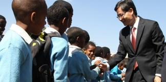 La Yifan, Chinese Ambassador to Ethiopia, shakes hands with Ethiopian young children during a ceremony in Addis Ababa, Ethiopia, Nov. 20, 2015. La Yifan said China would continue to strengthen its cooperation with Ethiopia and Africa in general in education and human resource development. The Ambassador made the remarks on Thursday at a ceremony organized to celebrate the accomplishment of Chinese-funded pavement and road on the premises of a primary school namely Tinbite Ermiyas Primary School in Ethiopia's capital Addis Ababa. (Xinhua/Michael Tewelde)