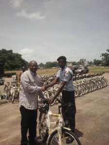 Dr Robert Kugnab, presenting one of the bicycles to a beneficiary