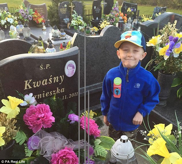 Missing mummy: Filip beside his mother Agnieska's grave in Poland where he wants to be buried