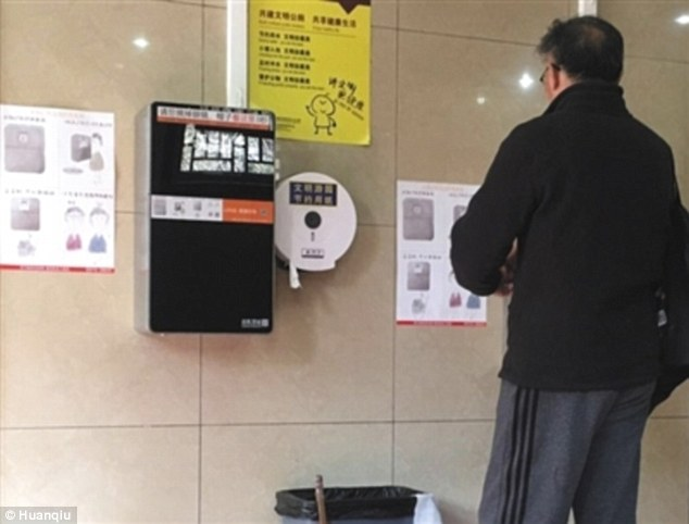Watching you: A toilet user reads the instructions for use of the smart paper machine
