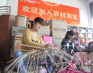 """Villagers of Wantou Village, Boxing county in east China's Shandong Province make crafts. The banner on the wall reads """"Welcome to join Taobao"""". (Photo by official website of Boxing county)"""