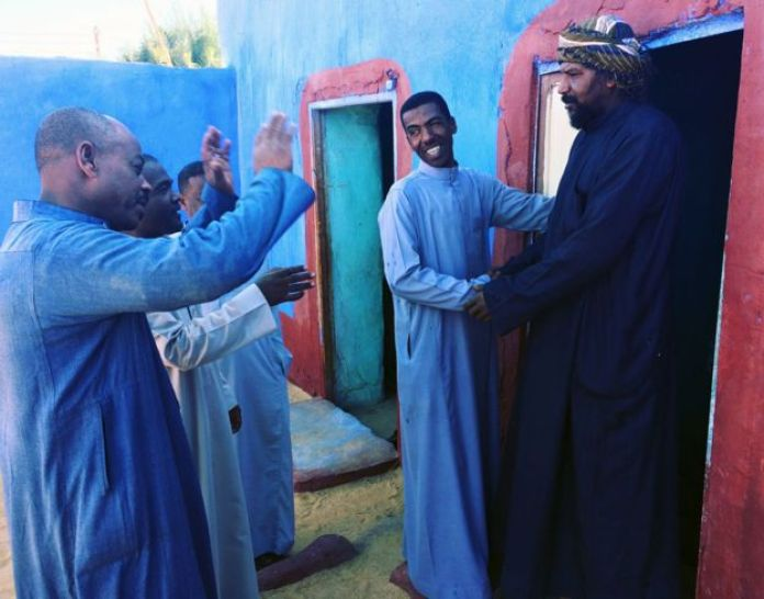 Akram (centre) goes from house to house with friends to invite people to his wedding