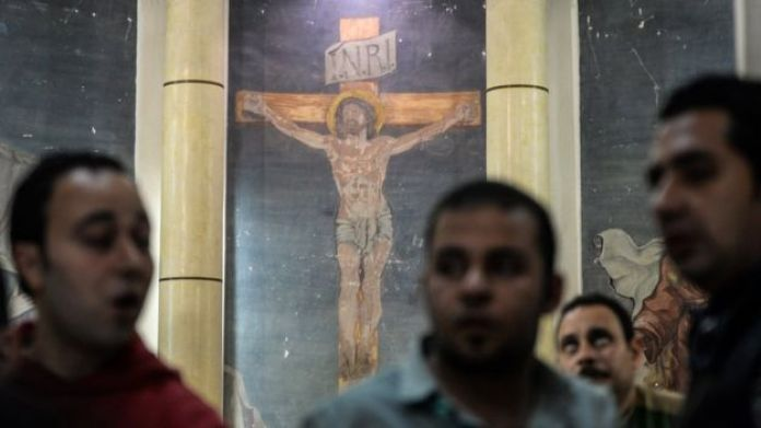 People gathered to view the damages at the scene of a bomb explosion inside Mar Girgis church in Tanta
