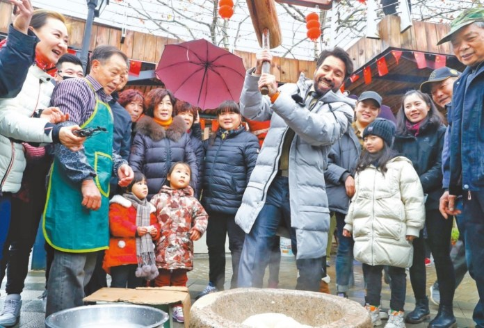 A foreign tourist learns to make sticky rice cake during a folk culture festival held in Moganshan township, Deqing county, Huzhou city in east China's Zhejiang province. Tourists there also experienced dragon dance, learned to make dumplings and cakes, and watched performance during the festival. Photo by Xie Shangguo from CPANET.CN.
