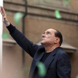 Former Italian Prime Minister Silvio Berlusconi waves during a rally to protest his tax fraud conviction, outside his palace in central Rome