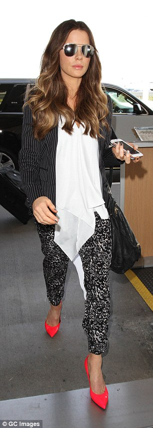 The 42-year-old beauty layered a flowing, white top underneath a pinstriped blazer, which she left unbuttoned