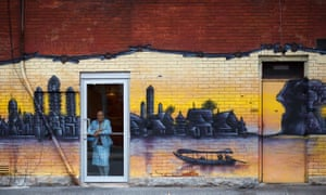 A woman looks a window surrounded by a mural in Chinatown in Ottawa, Canada, October 7, 2018. (Cole Burston)