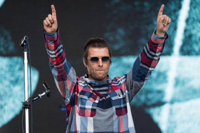 Liam Gallagher on stage at Glastonbury Festival 2019 holding his hands up in the air