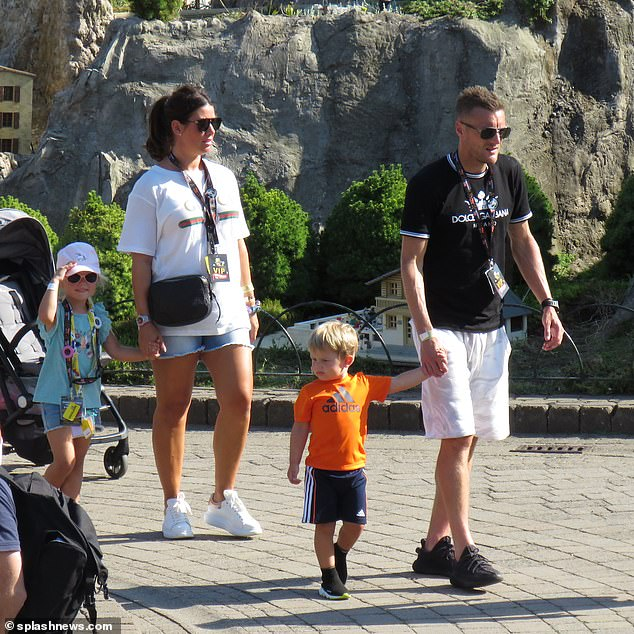 Famous four: Rebekah and Jamie held hands with their children as they made their way around the park
