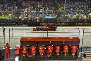 Ferrari crew monitor the action as Charles Leclerc drives past.