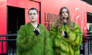 Two young women, not wearing makeup, wear coats that look much like fur coats but are green and striped yellow-green in front of red London Fashion week logo