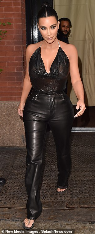 How low can you go? Kim showcased her upper assets in a shimmering black top which dipped low to reveal maximum amounts of cleavage