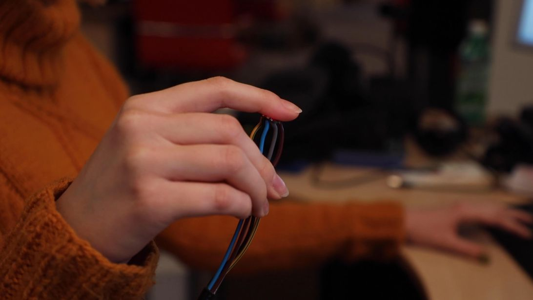 A hand holding wires with sensors for monitoring physiological responses