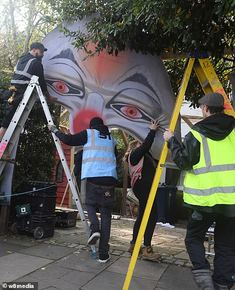 Working hard: The workers used ladders to put the clown face gate up without any injuries