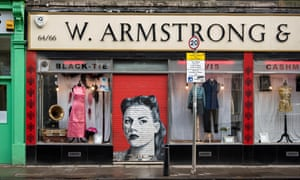 Armstrongs vintage clothing store with the shutter down revealing a retro protrait of a young woman.M4C074 Armstrongs vintage clothing store with the shutter down revealing a retro protrait of a young woman.