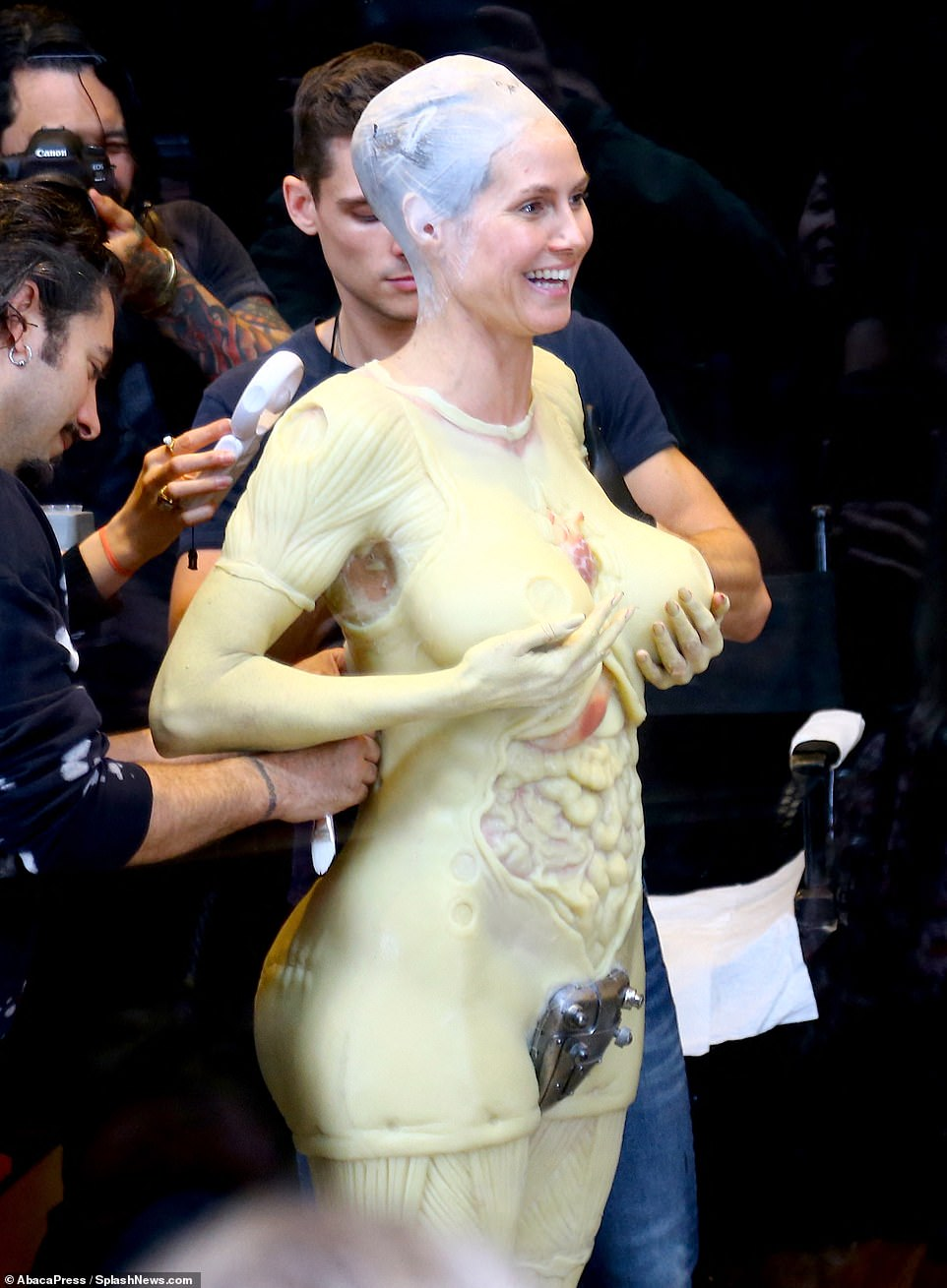 Is this ok? She touched her fake breasts and smiled while her crew worked on her
