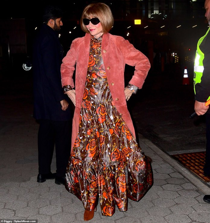 Bundled up: Anna Wintour kept out the chill with a long, comfy red–orange coat