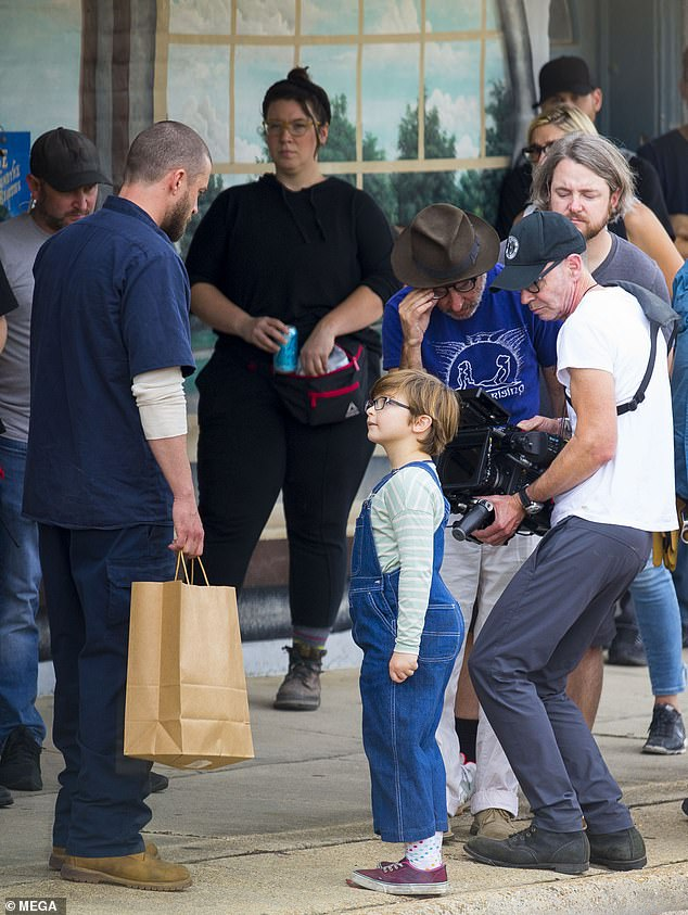 Unlikely dad: On Wednesday Justin filmed with the young actor who plays Sam, the son of his junkie neighbor, as director Fisher Stevens checked out the shot