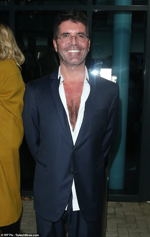 Slender:Simon put on a dapper display as he donned a dark blue blazer that he buttoned up over an open-collared white shirt that showed off his chest
