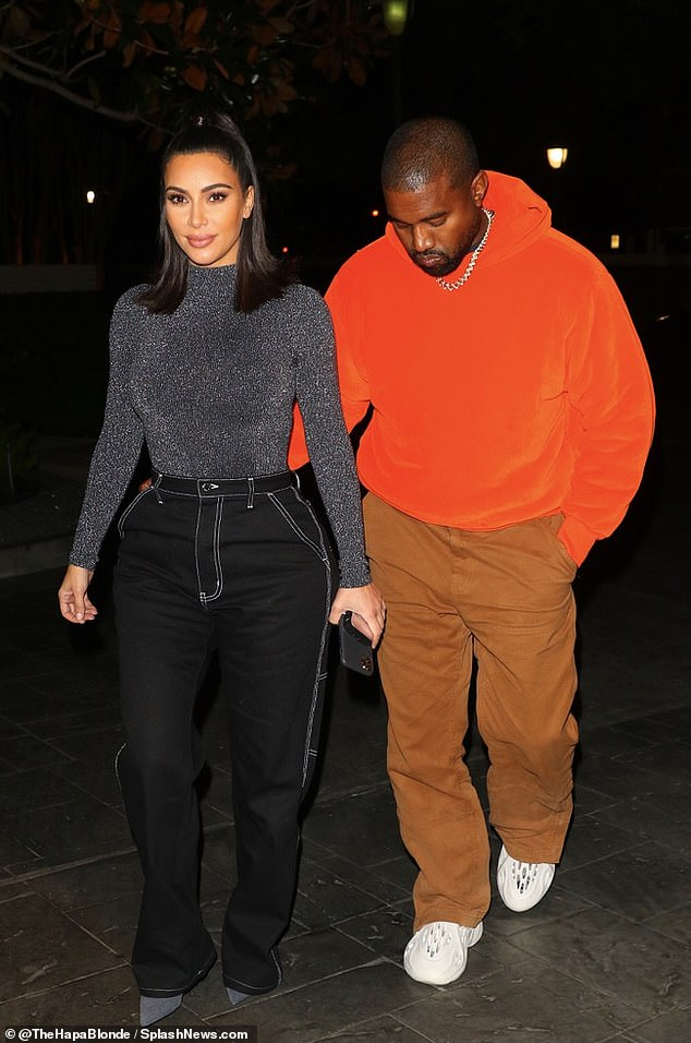 Stylish:The KKW Beauty entrepreneur teamed the look with grey pointed-toe boots and carried her phone in her hand