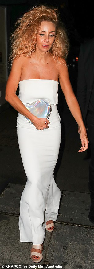 Accessories: The former reality star carried a heart-shaped purse in a holographic material and wore strappy pink heels