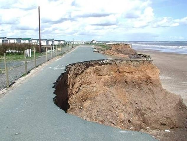 Experts found that the east coast is being hardest hit, with the erosion rate the fastest in Yorkshire and the Humber, where 56 per cent of the coastline is at risk. Pictured, a road collapsing into the ocean at Skipsea Cliff, near Hornsea, in the East Riding of Yorkshire