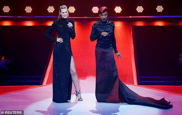 Ensemble:On stage, Toni debuted her second look of the night, cutting an elegant figure in a stunning black long-sleeved dress with a shimmering detail and a leg slit