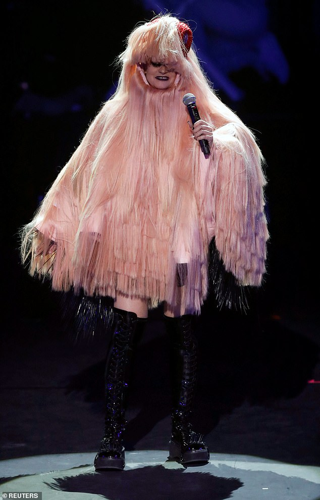 Elaborate: In one outfit, she donned a pink poncho-style garment with a hood and tassels