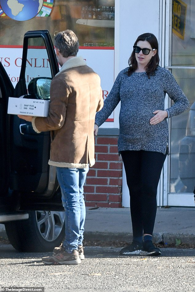 Baby on board!Anne Hathaway was positively beaming as she stepped out to run errands with her husband Adam Shulman in Connecticut on Monday morning