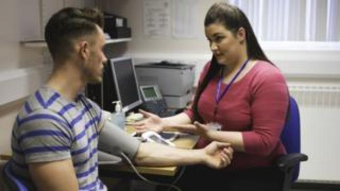 GP taking blood pressure of patient