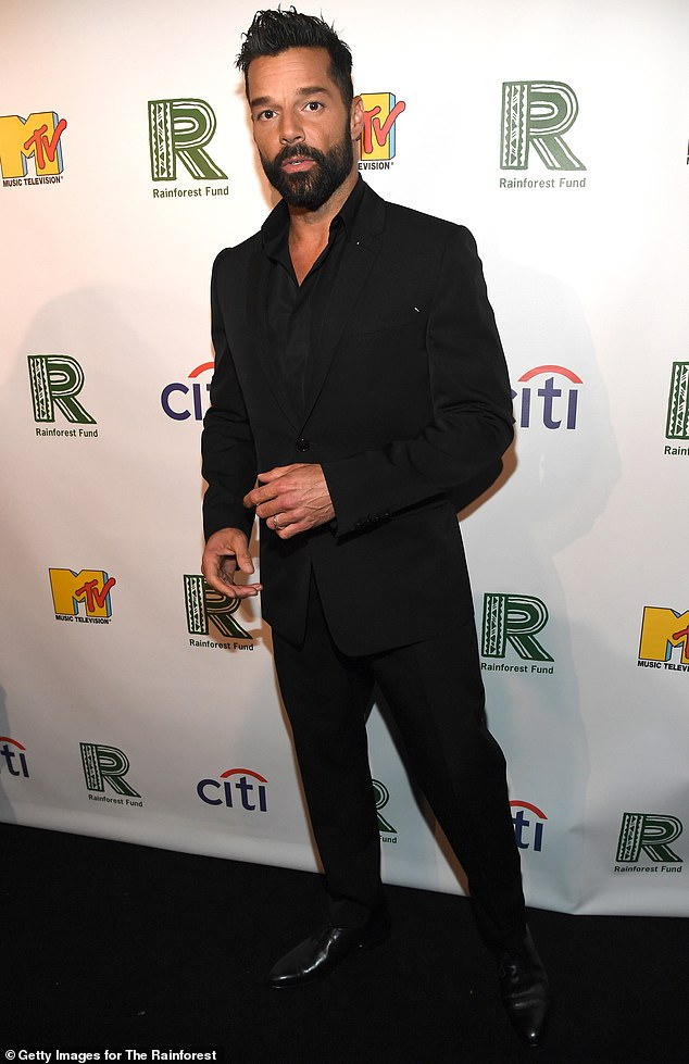Sexy look: Ricky Martin cut a sexy look in a tailored black suit, paired with patent leather black dress shoes