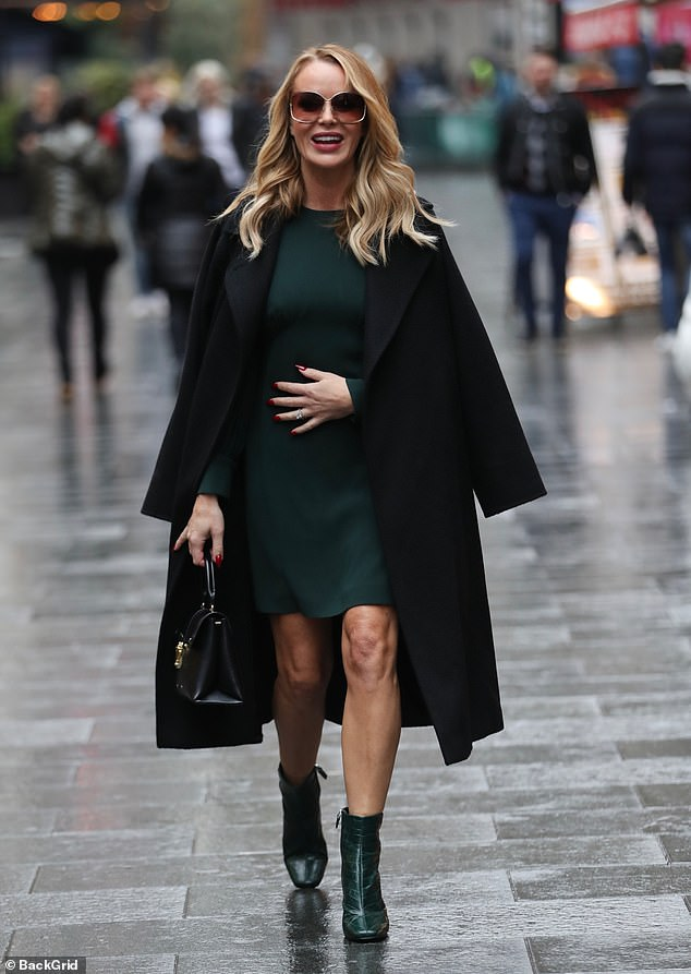 High spirits:The presenter, 48, smiled as she exited her daily breakfast show with a large black coat wrapped around her shoulders