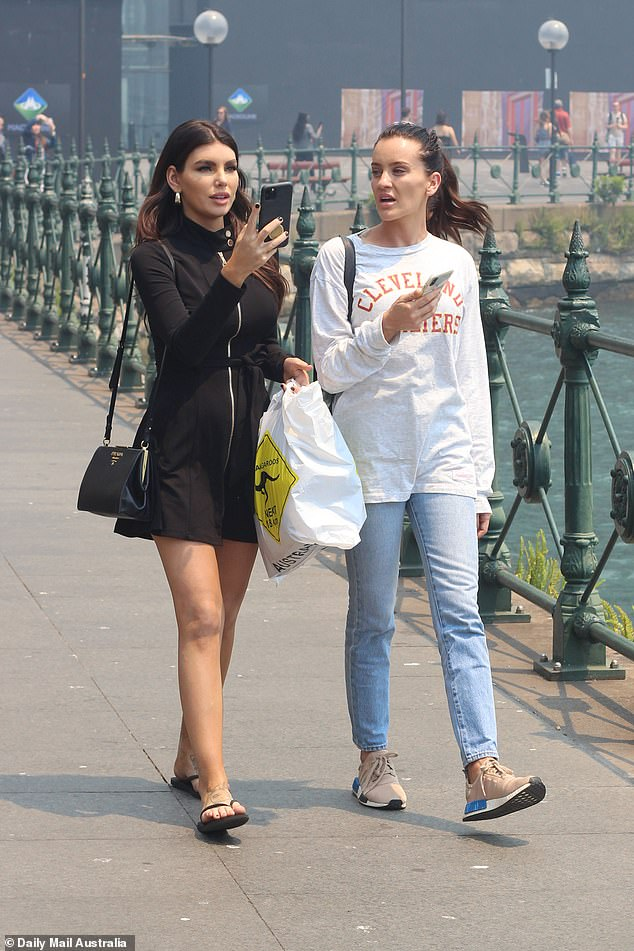 Influencers: The brunette was photographed in the haze on Thursday alongside Instagram model Nicole Thorne (left), who joined her for the whirlwind trip to Sydney