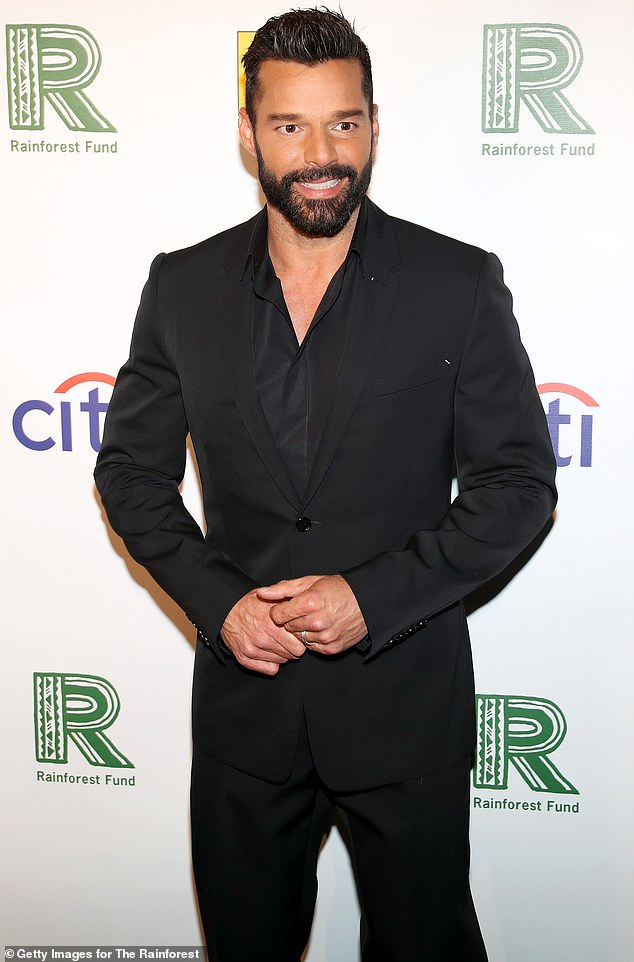 Chest hair: He wore the suit with a black dress shirt, unbuttoned at the top with no tie, revealing a hint of chest hair