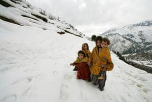 Girls walk in the snow near Kuz Ganrshal, Pakistan, 2006