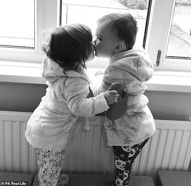 A devastated mother has shared a heartbreaking photograph (seen above) of her twins, 3, kissing after one was diagnosed with a rare form of leukaemia